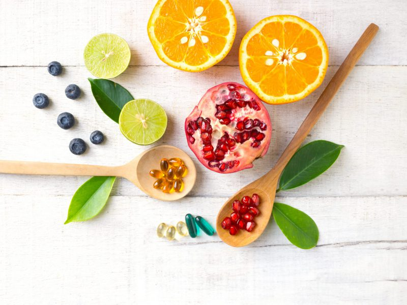 Multivitamin supplements on wooden spoon with healthy fruit blueberry, lime, orange, pomegranete on white wooden background.
